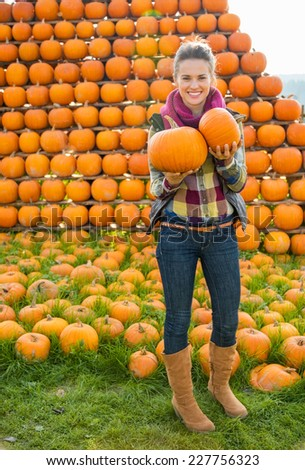 Portrait of happy young woman with pumpkins - stock photo