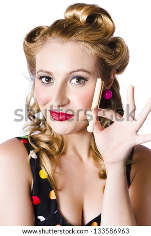 Portrait of happy young woman with retro hairstyle and clothes peg, white background - stock photo