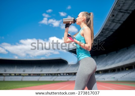 Portrait of healthy fitness girl drinking protein shake during workout on stadium - stock photo