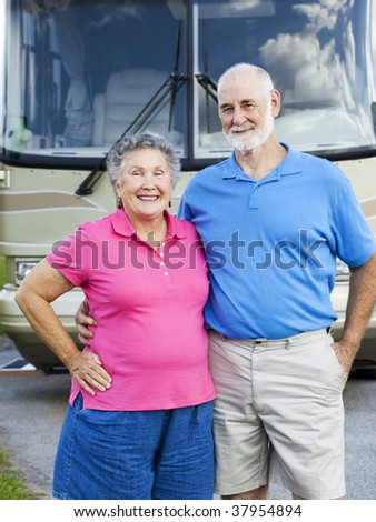 Portrait of healthy retired couple in front of their motor home. - stock photo