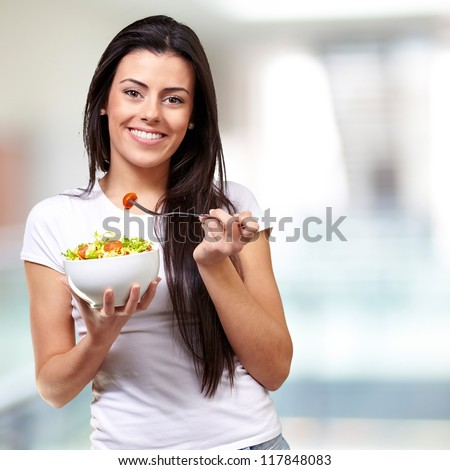 portrait of healthy woman eating salad indoor - stock photo