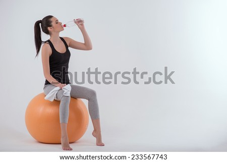 Portrait of healthy young sportswoman after doing exercises   sitting  on  orange exercise  ball  with towel drinking  bottle of mineral water isolated on white background full length   - stock photo