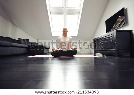 Portrait of healthy young woman exercising yoga in living room. Fitness female relaxing with yoga meditation at home. - stock photo