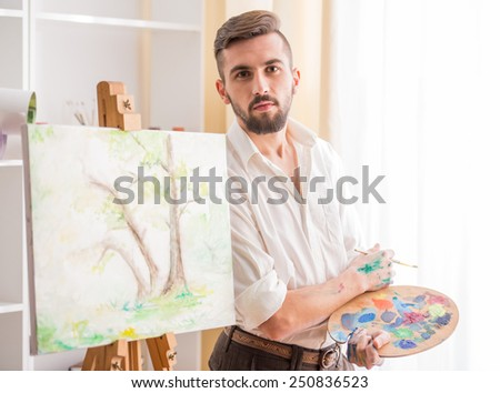 Portrait of highly gifted painter is holding brush and palette in his hand is finishing his picture. - stock photo