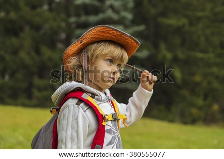 Portrait of hiking kid boy with backpack in autumn forest - stock photo
