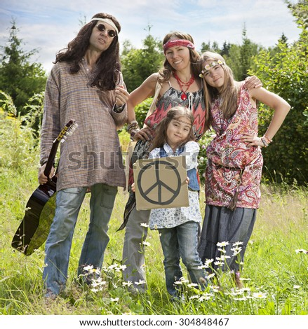 "Portrait of hippie family standing in the field with ""Pacific"" sign 
