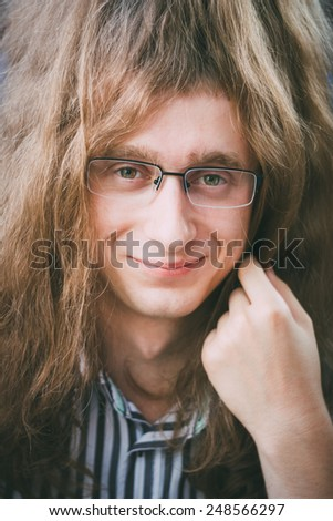 Portrait Of Hippie Hippy Young Man Guy With Glasses And Long Hair Smiling And Looking At Camera - stock photo