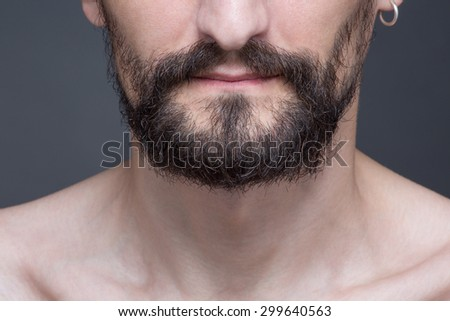 Portrait of hipster bearded man. Close-up cropped image of bearded man's face isolated on dark grey. - stock photo