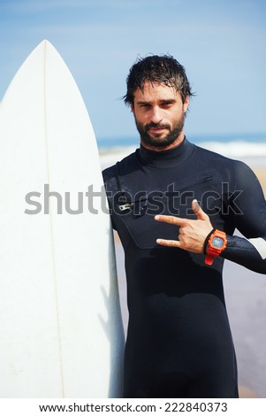 Portrait of hipster guy with white surfboard standing on ocean the beach, professional surfer man dressed in wetsuit ready to surfing on big waves, happy surfer holding his board at sunny summer day - stock photo