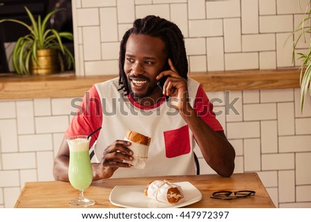 Portrait of hipster man on the phone while eating at cafe - stock photo