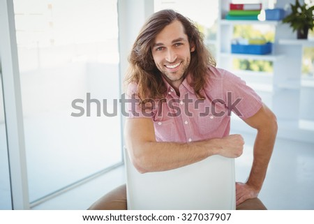 Portrait of hipster smiling while sitting on chair in office - stock photo