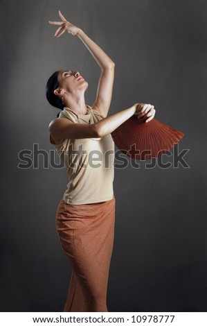 Portrait of hispanic flamenco dancer in traditional pose with fan - stock photo