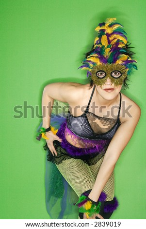 Portrait of Hispanic woman in Mardi Gras type costume and mask standing against green background. - stock photo