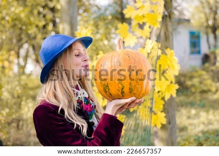 portrait of holding pumpkin elegant beautiful blond young hipster woman having fun happy smiling and looking at camera on autumn copy space outdoors background - stock photo