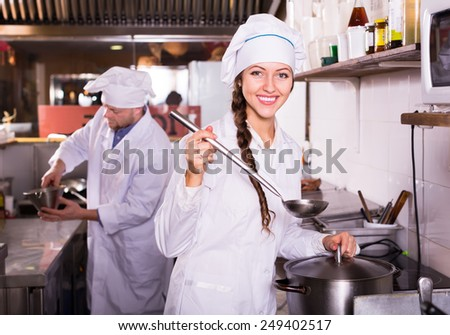 Portrait of hospitable chef with smiling young beautiful female helper at bistro kitchen