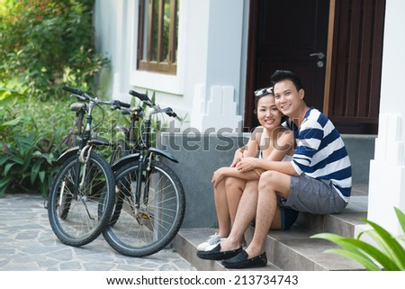 Portrait of hugging couple sitting on the porch with their bicycles nearby - stock photo