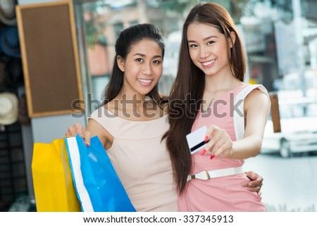 Portrait of hugging Vietnamese girls paying for purchases with credit card - stock photo