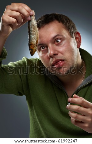 Portrait of hungry man staring at fish - stock photo