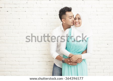 portrait of husband kissing his wife while hugging from behind with copy space - stock photo