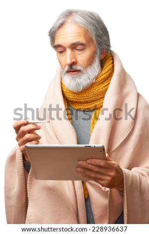 Portrait of Ill senior caucasian man covered with blanket holding thermometer and looking for doctor online by ipad tablet PC isolated on white background - stock photo