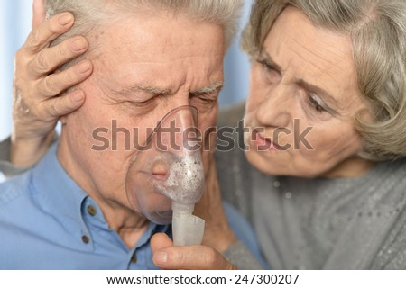 Portrait of ill senior couple, man with inhaler - stock photo