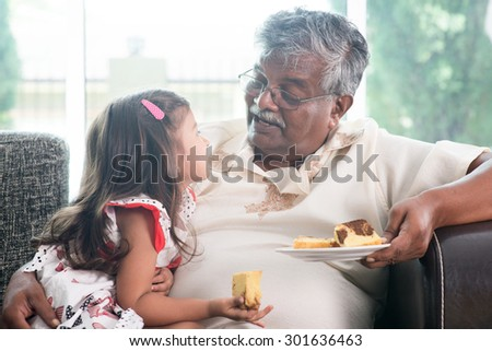 Portrait of Indian family at home. Grandparent and grandchild eating butter cake. Asian people living lifestyle. Grandfather and granddaughter. - stock photo
