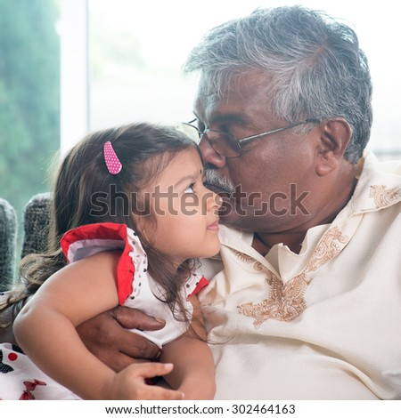 Portrait of Indian family at home. Grandparent kissing grandchild. Grandfather and granddaughter. Asian people living lifestyle. - stock photo