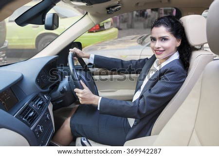 Portrait of indian young woman smiling at the camera while driving her car - stock photo