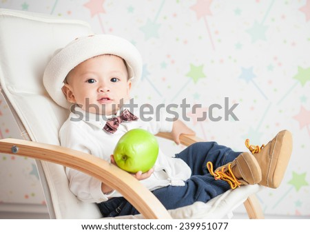 Portrait of infant baby boy looking smiling happy. Asian child holding apple and sitting on the chair - stock photo