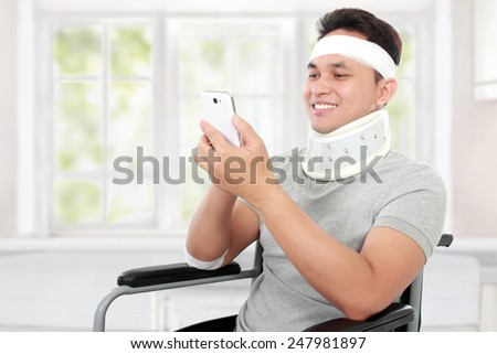 portrait of injured young man play on his smartphone - stock photo