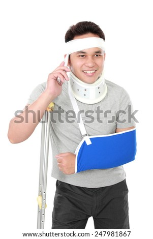 portrait of injured young man talking on the phone on white background - stock photo
