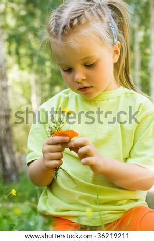 Portrait of innocent girl looking at flowers in her hands - stock photo