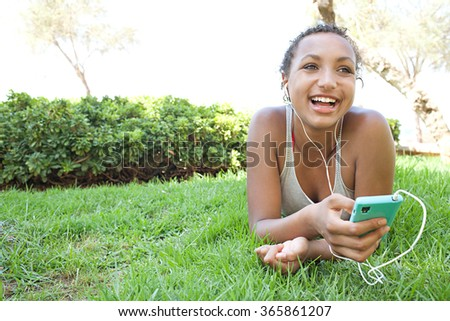 Portrait of joyful african american teenager girl using smartphone and headphones to listen to music, smiling laying on grass in park, outdoors. Adolescent technology lifestyle, exterior holiday. - stock photo