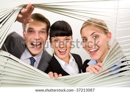 Portrait of joyful business partners looking at camera out of venetian blind - stock photo