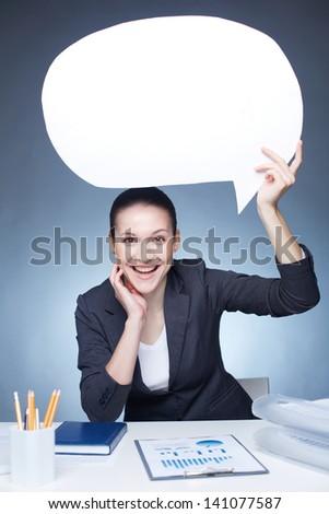 Portrait of joyful businesswoman holding paper speech bubble at workplace - stock photo