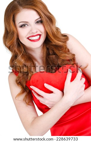 portrait of joyful cheerful cute woman with red hair bright make up and red lips holding red heart in hands. portrait of attractive caucasian smiling woman brunette isolated on white studio shot - stock photo