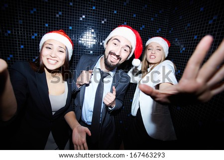 Portrait of joyful colleagues in Santa caps dancing at Christmas party  - stock photo