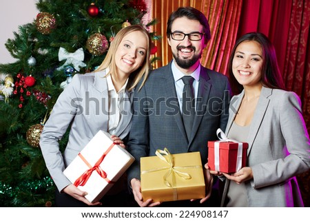 Portrait of joyful colleagues with giftboxes standing by xmas tree - stock photo
