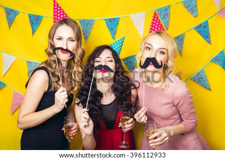 Portrait of joyful friends toasting and looking at camera at birthday party. Attractive friends celebrating a birthday. Smiling girls. Celebration and party. Having fun.  - stock photo