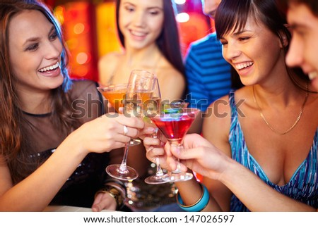 Portrait of joyful friends toasting at birthday party, focus on two happy girls - stock photo