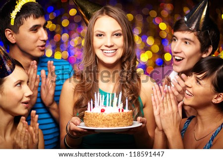 Portrait of joyful girl holding birthday cake surrounded by friends at party - stock photo