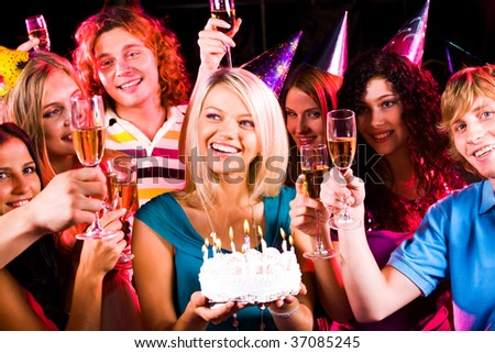 Portrait of joyful girl holding birthday cake surrounded by friends with flutes of champagne - stock photo