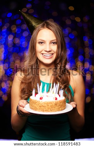 Portrait of joyful girl holding birthday cake with candles and looking at camera at party - stock photo