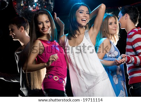 Portrait of joyful girls laughing while dancing at disco with their boyfriends - stock photo