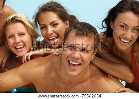 Portrait of joyful guy and happy girls on background looking at camera on summer vacation - stock photo