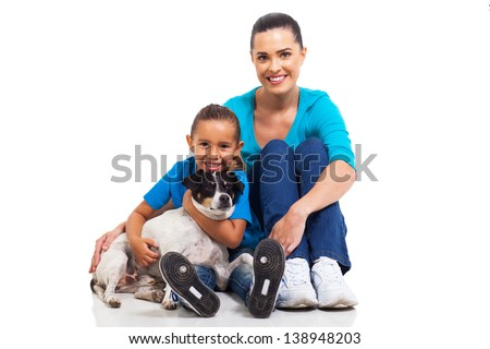 portrait of joyful mother sitting with her little daughter and pet dog on white background - stock photo