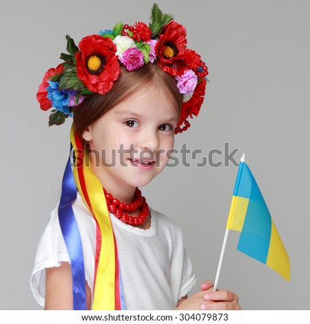 Portrait of joyful young girl in the Ukrainian national clothes on gray background - stock photo
