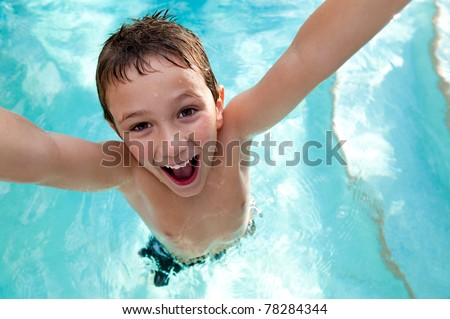 Portrait of kid very playful and jumping in a swimming pool. - stock photo