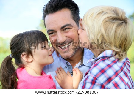Portrait of kids giving a kiss to their daddy - stock photo