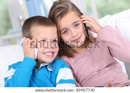 Portrait of kids talking on mobile phone - stock photo